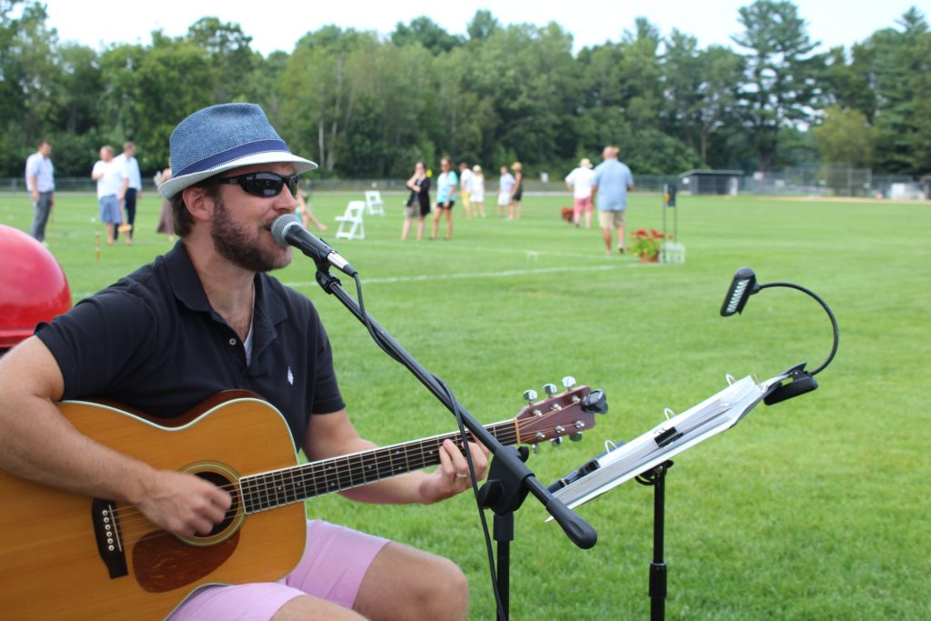 Side shot of Thomas Powers singing and playing guitar at Croquet on the Green 2019