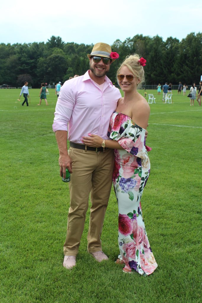Couple with pink outfits and matching pink flowers in their hair and hat smiling at Croquet on the Green 2019