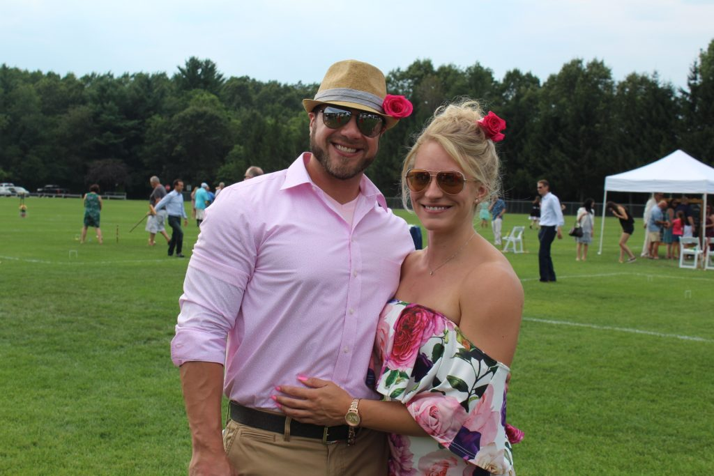 Woman in floral off the shoulder dress with pink flower in her hair smiling and holding her boyfriend with pink shirt and pink flower in his fedora hat at Croquet on the Green 2019