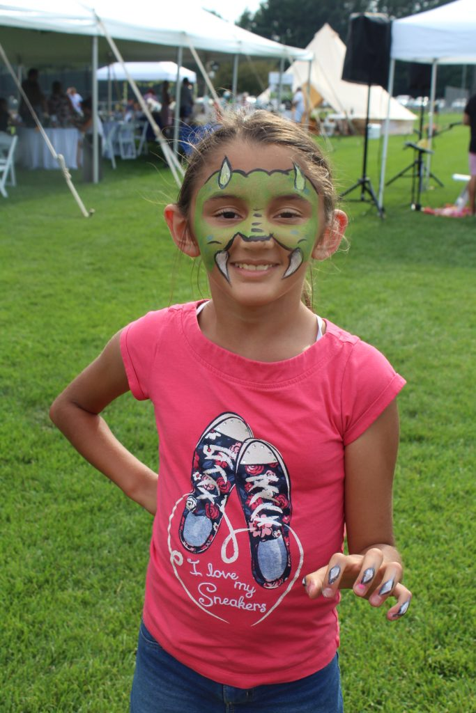 Young girl with dragon face paint on at Croquet on the Green 2019