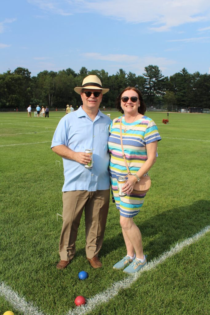 Couple holding beers on croquet field at Croquet on the Green 2019