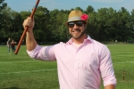 Man in pink shirt with tan fedora and a pink flower in the hat holding a croquet mallet in the air and smiling at Croquet on the Green 2019
