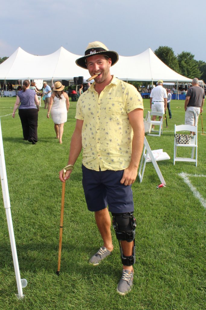 Man in yellow shirt and cigar in mouth smiling at Croquet on the Green 2019