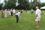 Ramon Dominguez hitting croquet ball as Croquet expert and group of people watch at Croquet on the Green 2019