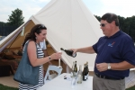 Brian Gwynn of Specialty Wines and More pouring sparkling wine for a woman in front of the glamping tent at Croquet on the Green 2019