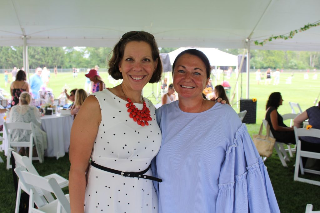 Woman in a white dress and red beaded necklace smiling with a woman in a blue blouse at Croquet on the Green 2019
