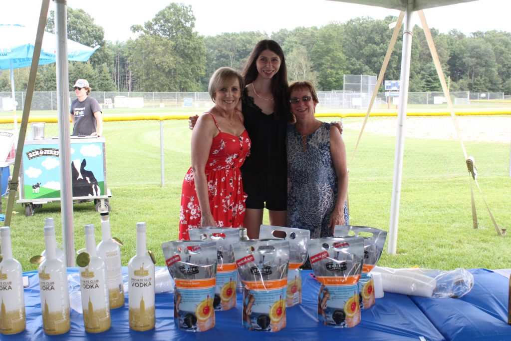 Group of three womens standing in front of table with vodka on it at Croquet on the Green 2019