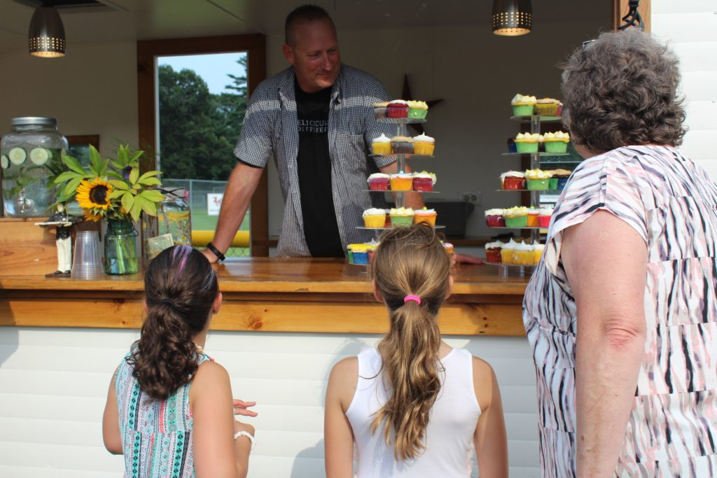 Older woman with two young girls looking at stacks of cupcakes as a man behind the counter looks on at Croquet on the Green 2019