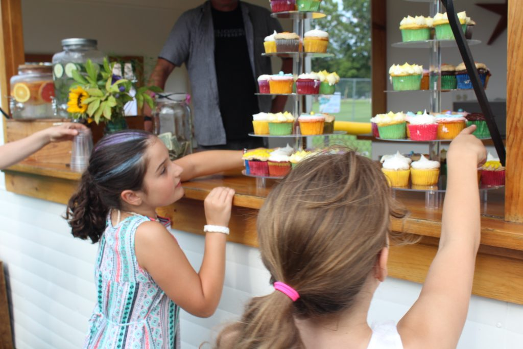 Two young girls looking at cupcakes at Croquet on the Green 2019
