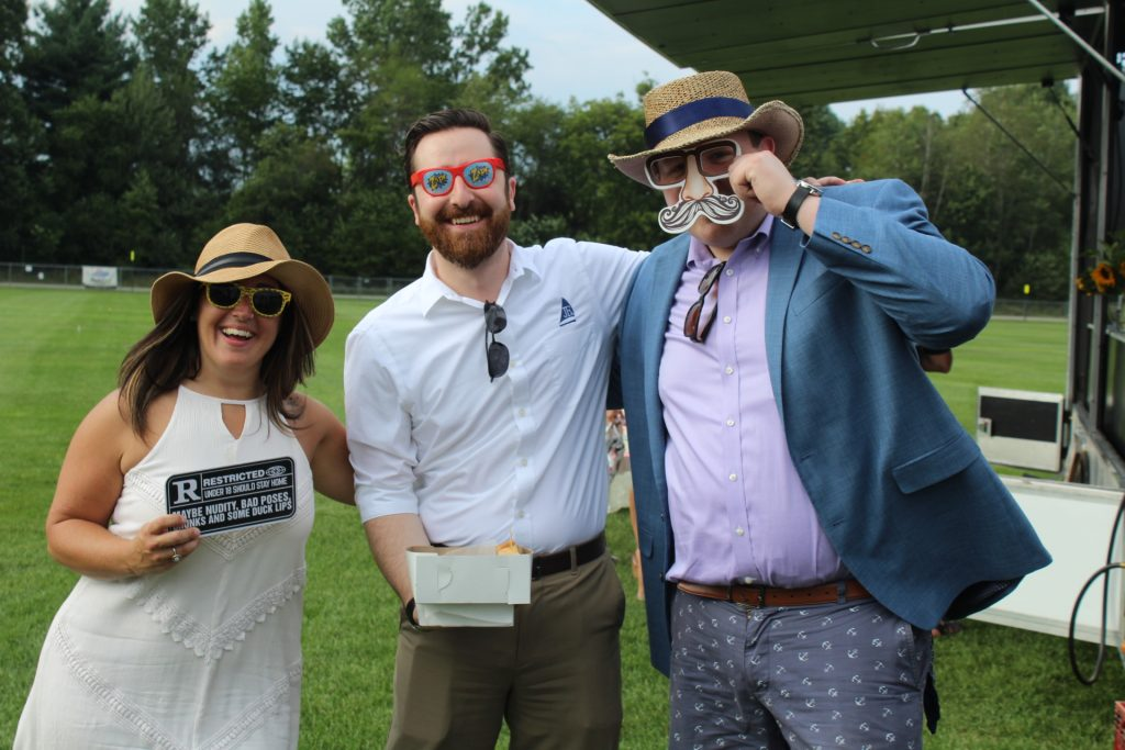 Group of three people with goofy glasses and a sign from the photo booth at Croquet on the Green 2019