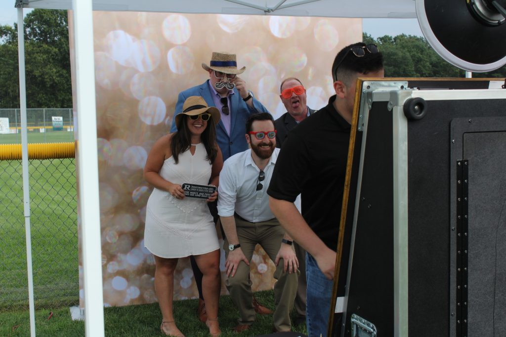 Group of four people taking a photobooth picture at Croquet on the Green 2019