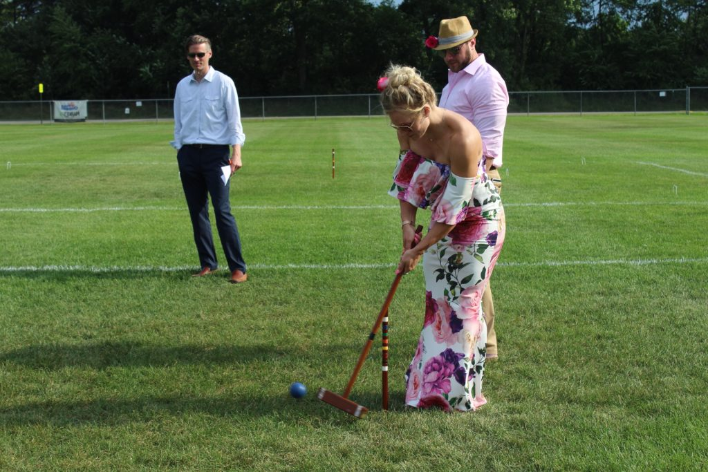 Woman in floral dress hitting croquet ball at Croquet on the Green 2019