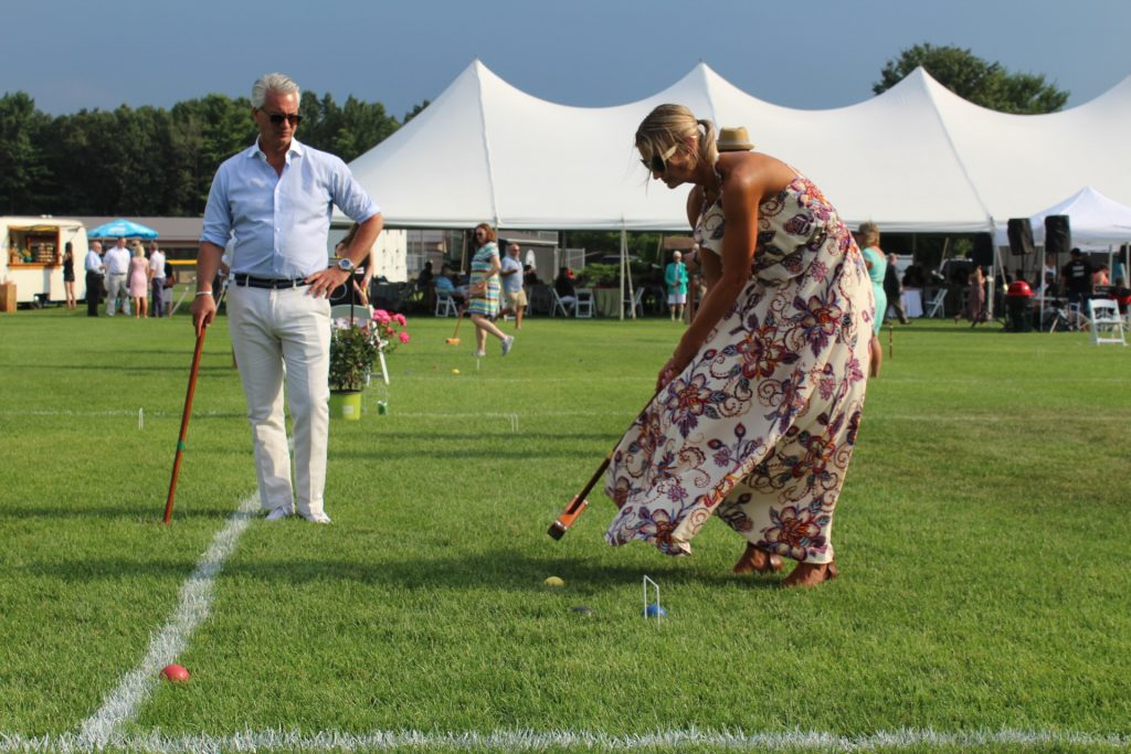 Woman hitting croquet ball with man looking on at Croquet on the Green 2019