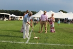 Man hitting croquet ball as group of three people look on at Croquet on the Green 2019