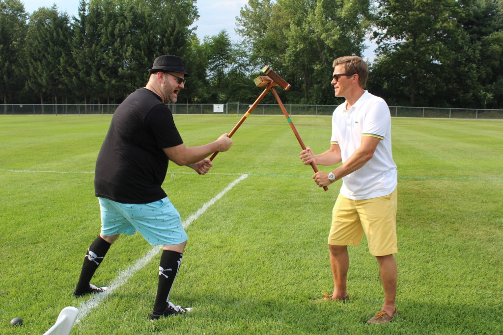 Two men holding croquet mallets up like swords at Croquet on the Green 2019