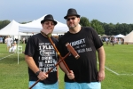 Two men holding croquet mallets in a crossed X wearing matching black fedoras at Croquet on the Green 2019