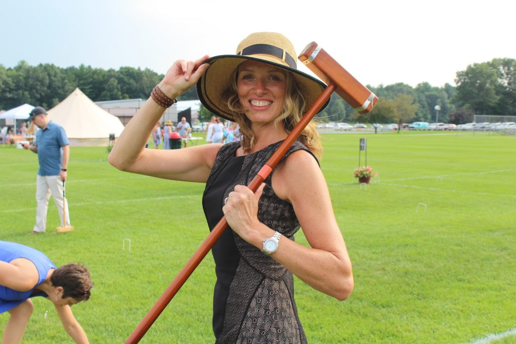 Woman with brimmed hat posing with croquet mallet