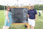 Two people standing in front of a large chalkboard sign that has a bracket of team names on it at Croquet on the Green 2019