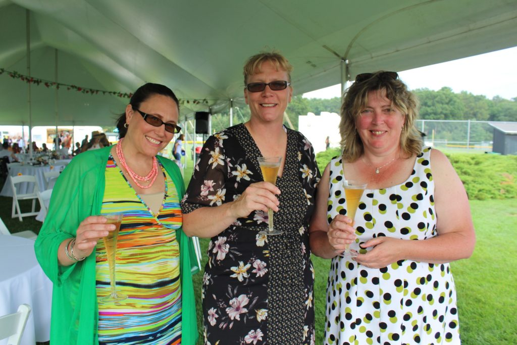 Three women holding glasses of champagne at Croquet on the Green 2019