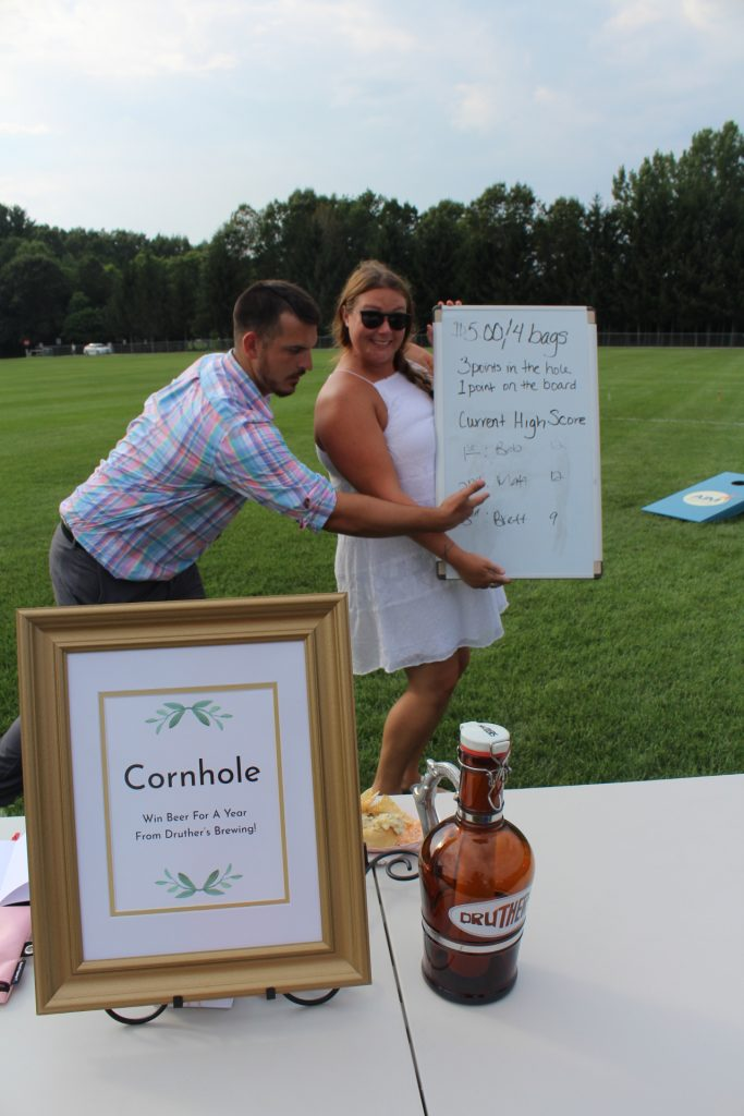 Woman holding high score sign for cornhole while a man points at his place on the board at Croquet on the Green 2019