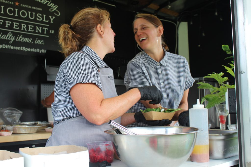 Caterers from Deliciously Different preparing food and looking at each other smiling at Croquet on the Green 2019