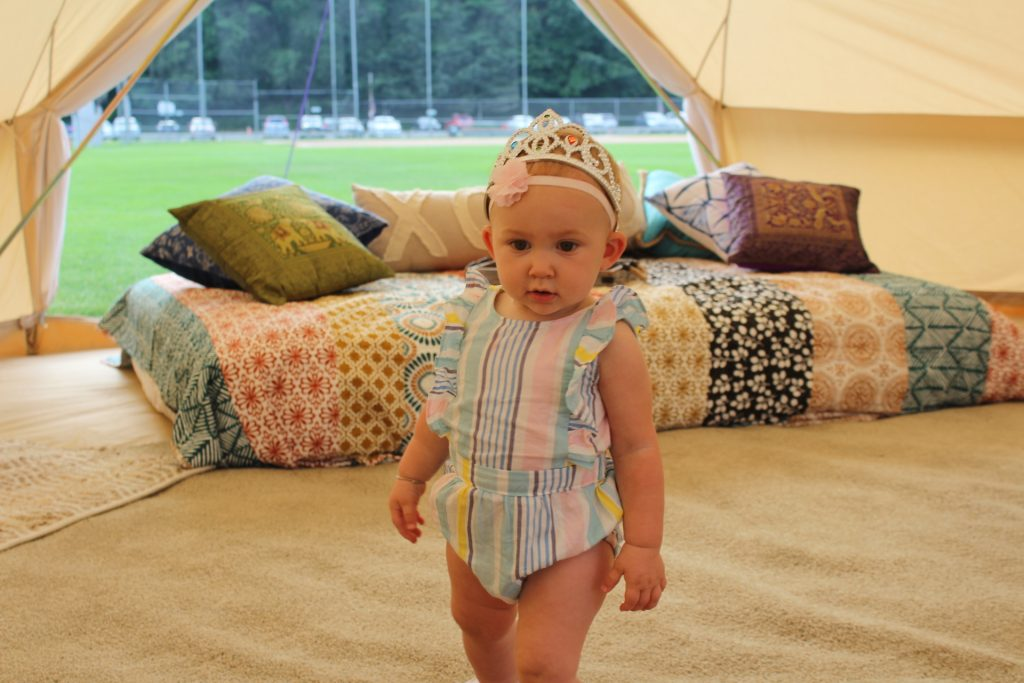 Baby in the glaping tent with a tiara on at Croquet on the Green 2019