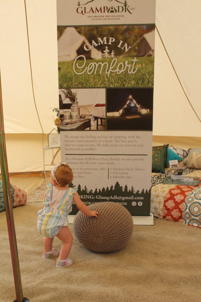 GlampADK sign with a baby standing in front at Croquet on the Green 2019