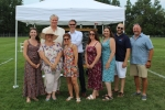 Group of nine AIM employees standing in front of white popup tent at Croquet on the Green 2019