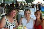 L-R: Noelle Fortier, June MacClelland, and Marissa Romero sitting at a table together smiling at Croquet on the Green 2019