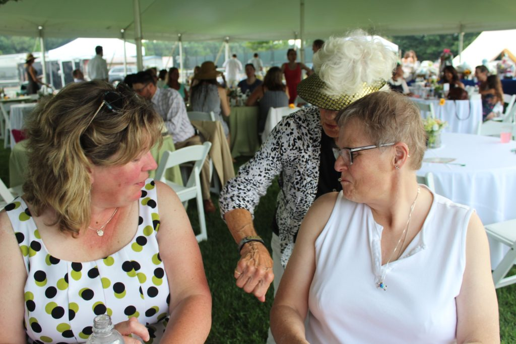 Woman showing two other woman her bracelet at Croquet on the Green 2019