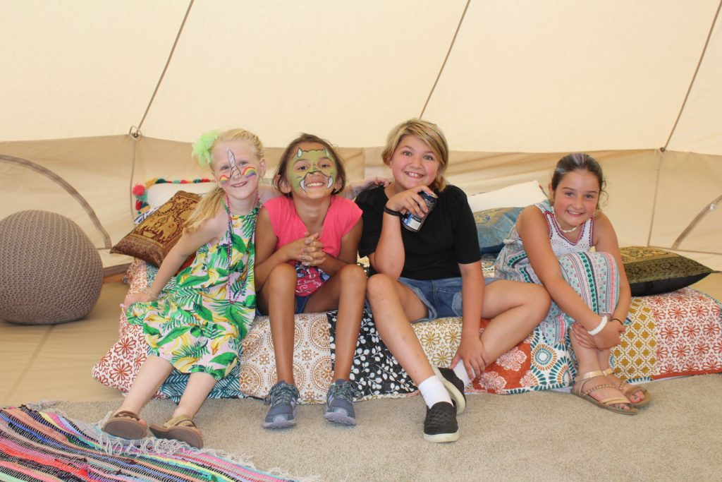 Group of four young girls sitting on bed in glamping tent at Croquet on the Green 2019