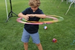 Young boy hula hooping with two hula hoops at Croquet on the Green 2019