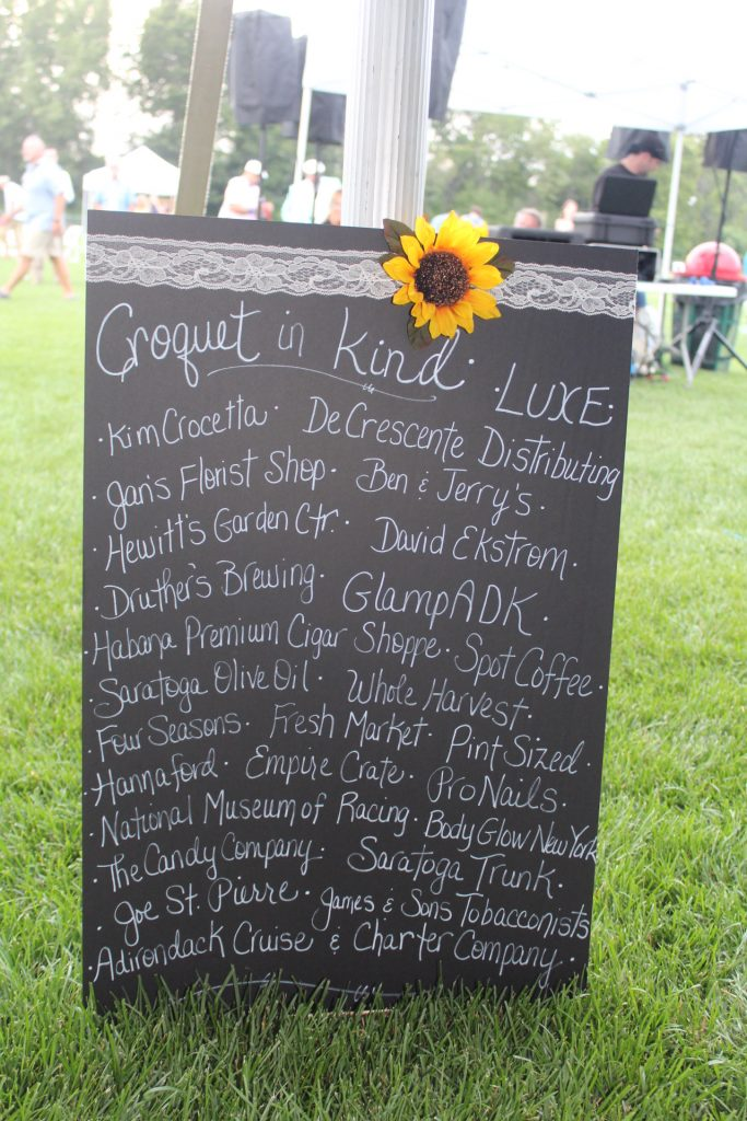 Black board sign with white lettering showing list of in-kind donors such as GlampADK, DeCrescente Distributing, ProNails and more at Croquet on the Green 2019