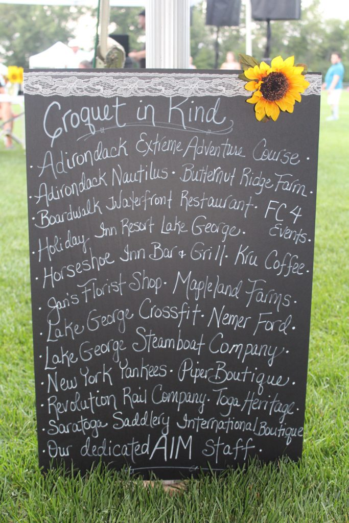 Black board sign with white lettering showing list of in-kind donors such as Adirondack Nautilus, Jan's Florist Shop, Lake George Crossfit and more at Croquet on the Green 2019