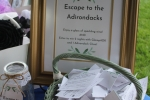 Sign for Escape the the Adirondacks package with a basket in front filled with entries to win the package at Croquet on the Green 2019