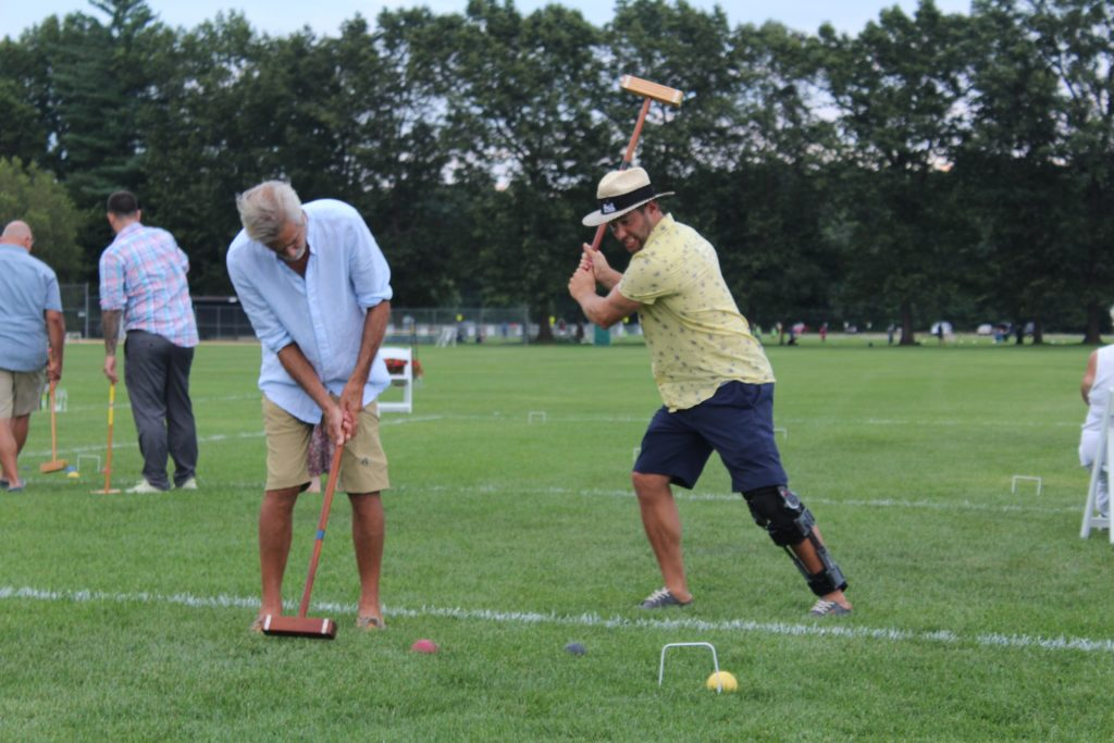 Man holding croquet mallet pretending to hit his opponent while he takes his shot at Croquet on the Green 2019