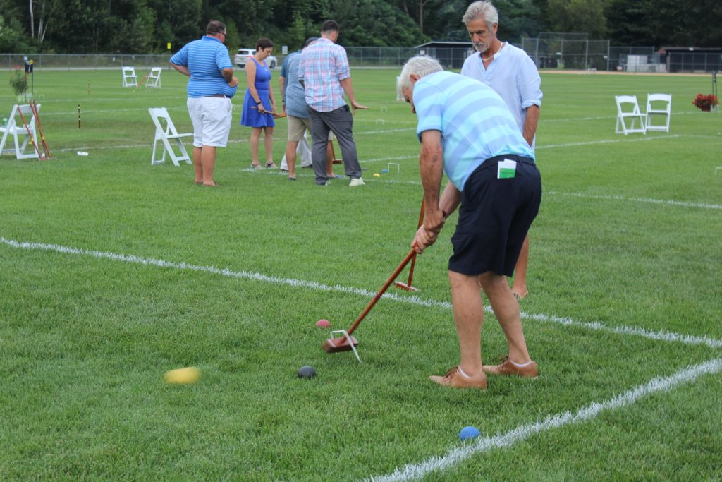 Man in a striped shirt takes a shot at croquet while another man looks on at Croquet on the Green 2019