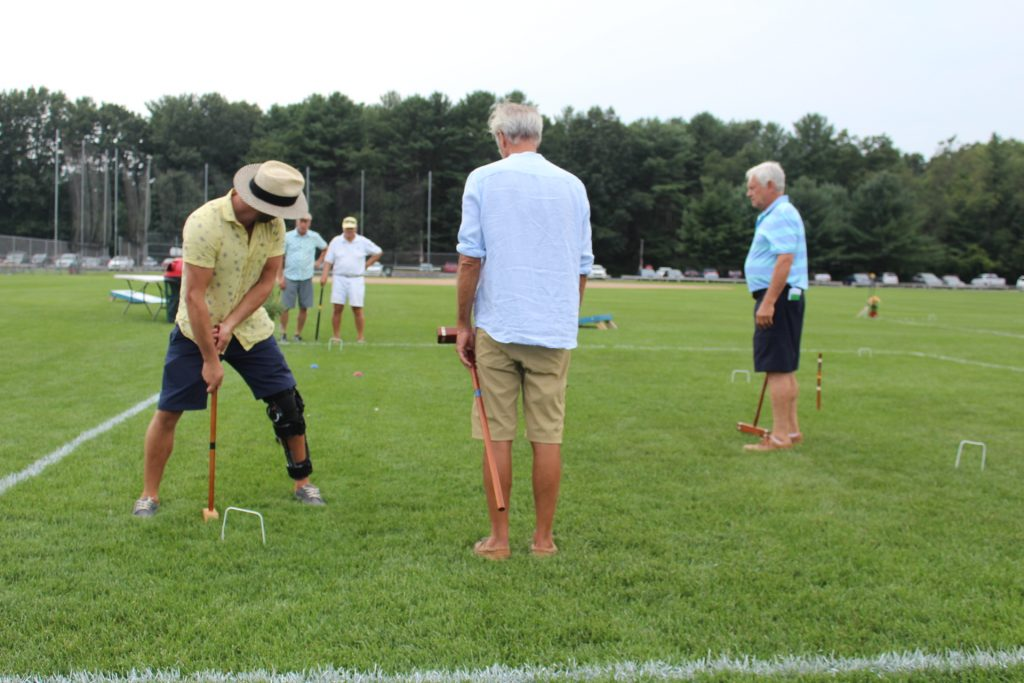 Man takes a backwards shot of croquet through his own legs at Croquet on the Green 2019