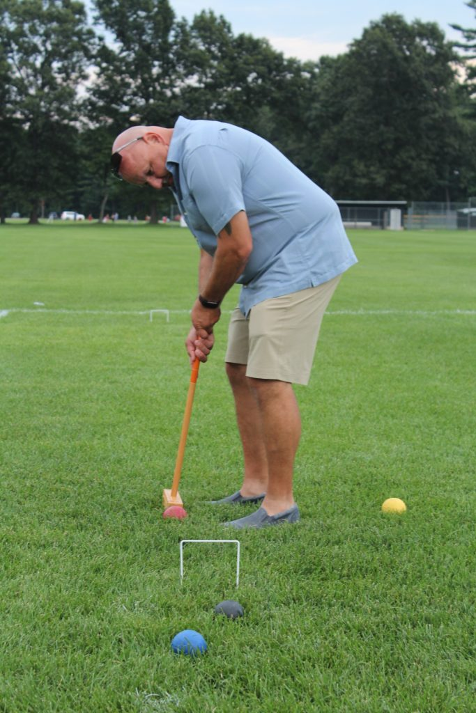 Man taking a shot at Croquet about to hit the ball through a wicket at Croquet on the Green 2019