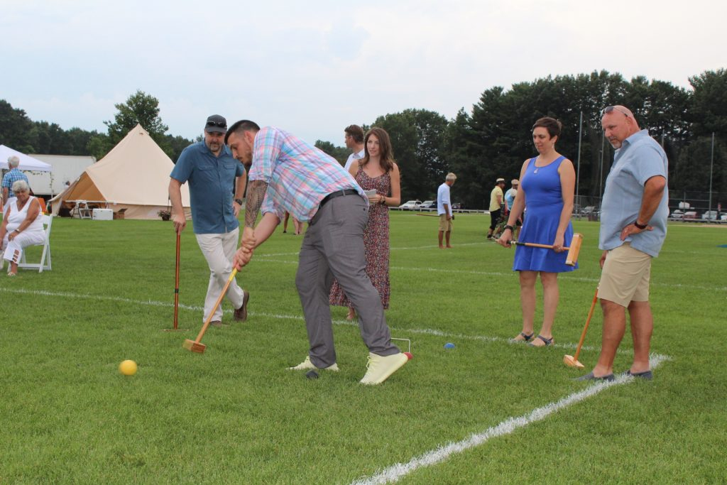 Man hitting croquet ball as a group of people watch on at Croquet on the Green 2019