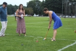 Woman in a blue dress taking a shot at croquet while two people look at at Croquet on the Green 2019