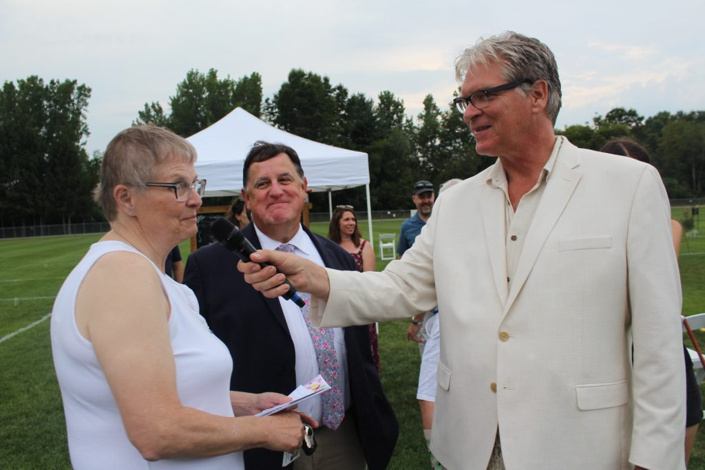 June MacClelland speaking into a microphone held by Walt Adams as Chris Lyons looks on smiling at Croquet on the Green 2019