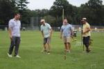 Group of four men looking at croquet balls on the field all laughing together at Croquet on the Green 2019