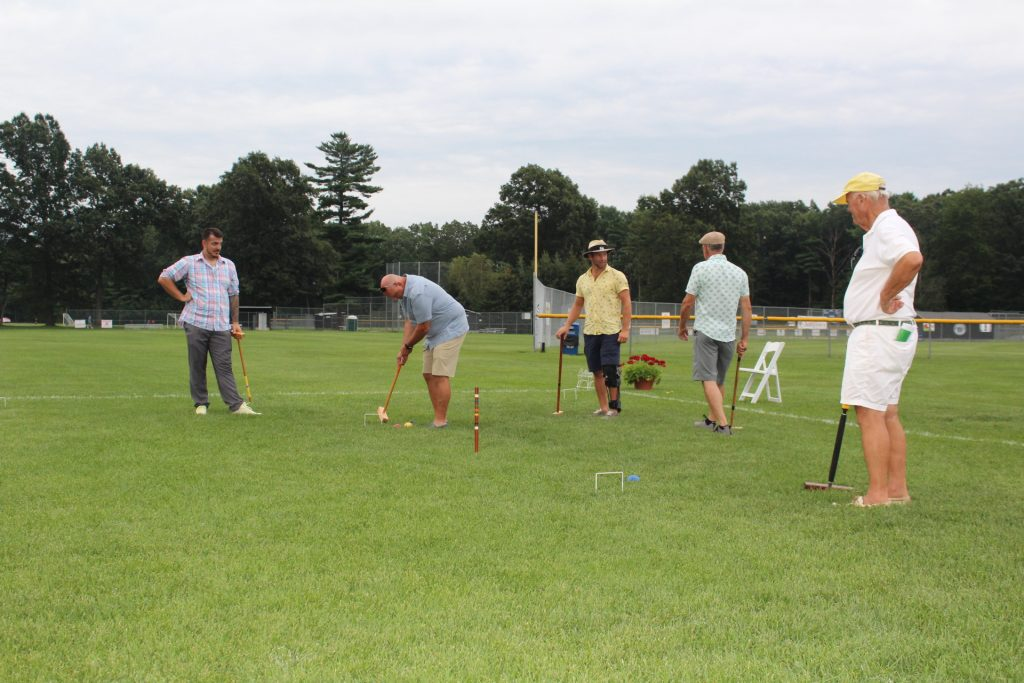 Man taking a shot at croquet as team mate, opponents, and croquet expert watches on at Croquet on the Green 2019