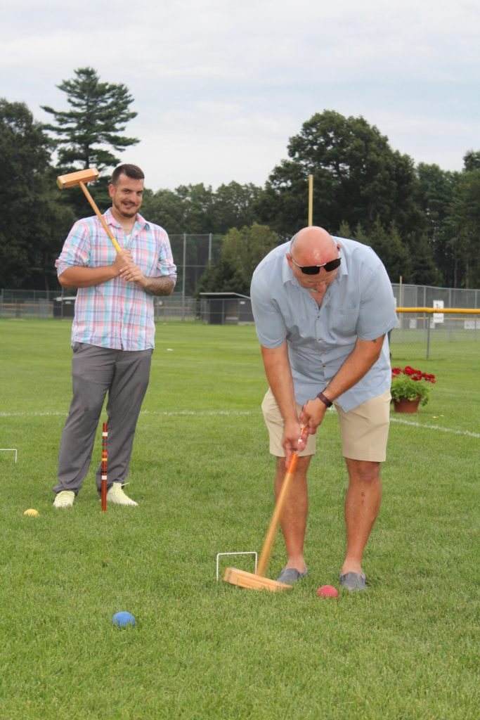 Bob Wiltsie bent over lining up his croquet shot while teammate stands behind him holding mallet at Croquet on the Green 2019