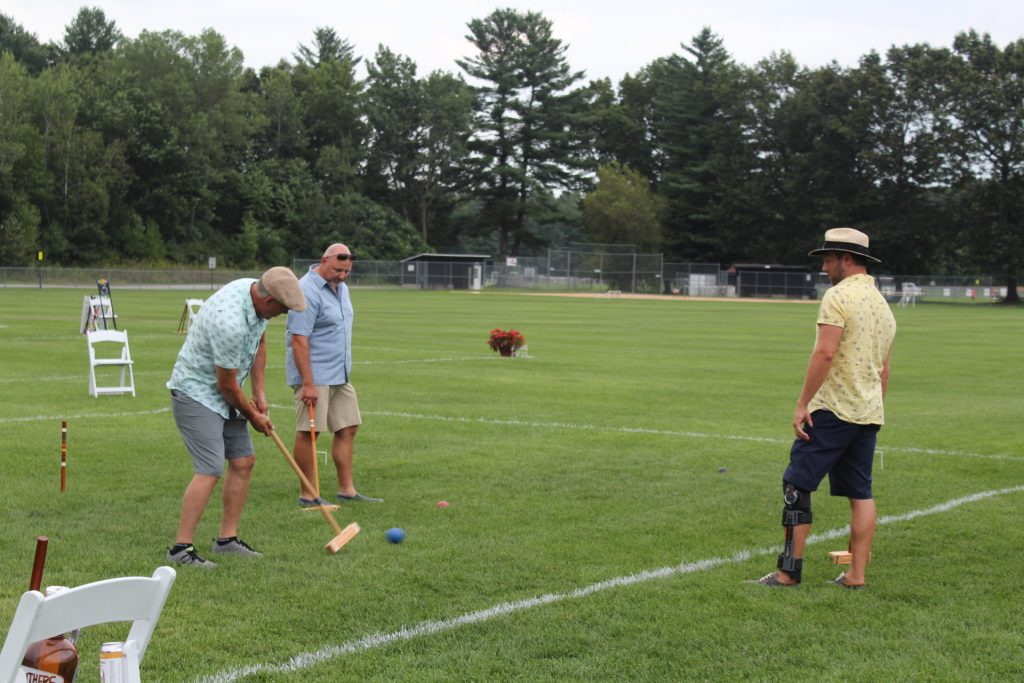 Man hitting croquet ball in the final tournament as teammate and opponent looks on at Croquet on the Green