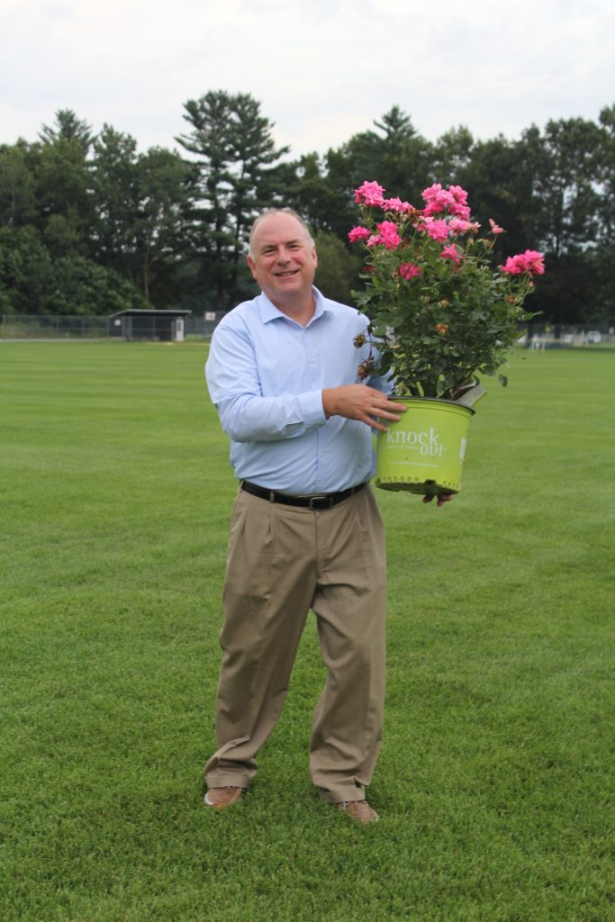 Scott Hartung holding a big pot of pink flowers at Croquet on the Green 2019