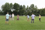 Man hitting croquet ball long distance as group of people look on at Croquet on the Green 2019