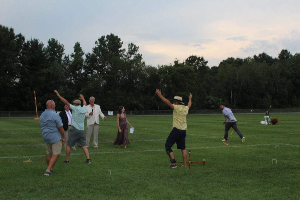 Winners of croquet final match throwing their hands into the air while losers have thrown their mallets aside as Walt Adam announces the of the game at Croquet on the Green 2019