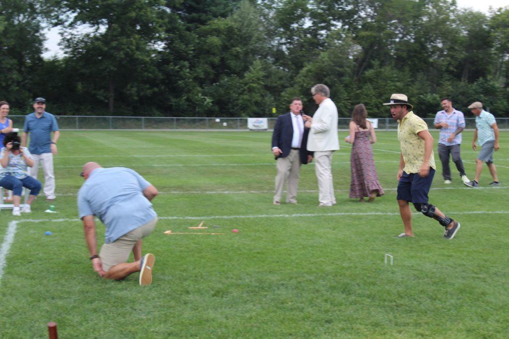 Man taking a knee on the field as person walks up to him at Croquet on the Green 2019